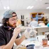Student sits at a workbench in the ceramics studio painting a sculpture piece.