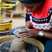 Student sitting at a pottery wheel using a tool to sculpt clay