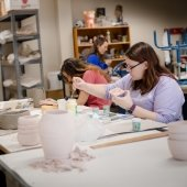 Three students sit at a workbench painting sculptures.
