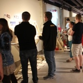 Students looking at their work on the wall while other students look on inside gallery b
