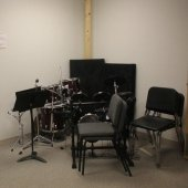 Chairs and music stands against a corner inside the Hagan Practice Room.