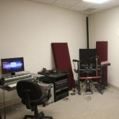 Another view of the Hagan Practice room with computer and desk with music stands and equipment.