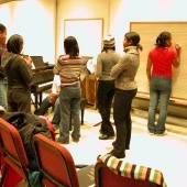 A group of students stand inside a rehearsal room talking while one writes on a chalkboard that has music bars