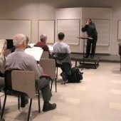 Conductor leading a seated choir in the Choral Rehearsal Room.