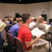 Side view of a seated choir in the Choral Rehearsal Room.