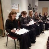 Seated choral performers in performance dress attire reviewing music before a performance in the Choral Rehearsal Room.