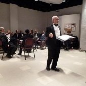 The conductor standing, preparing, before a performance in dress attire in the Choral Rehearsal Room.