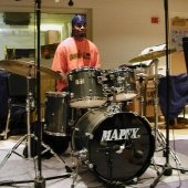Student sitting behind a drum set in the Instrumental Rehearsal Room.