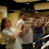 Four people standing playing trumpets in the Instrumental Rehearsal Room.