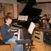 Student playing piano while other students play guitars in the Instrumental Rehearsal Room.