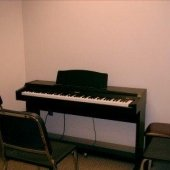 Inside one of the practice rooms that has a piano.