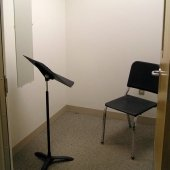 Inside one of the practice rooms that has a music stand and chair.