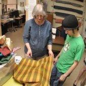 Faculty M.C. Friedrich showing a piece of fabric to a student.