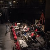 A view of the orchestra pit and the technical crew working with computers and sound equiptment.