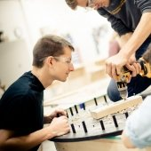 Two students observe as a third drills into a block of wood on a round, pegged project.