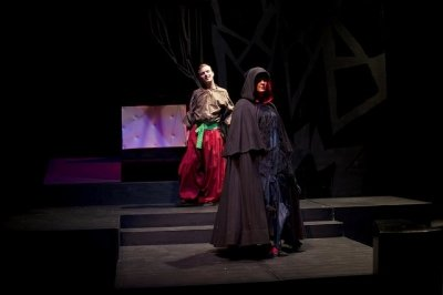 Two students standing on stairs on a stage, one in the foreground is in a cloaked hood, the other in a colorful costume.