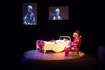 Students during a performance, one sitting next to someone else laying in a bed. Images projected on two screens above of other students performing.