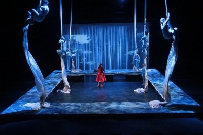 Single student standing in water on a stage, with four performers in each corner hanging on large strips of fabric